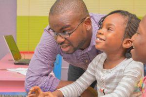 Ugochukwu Nkwocha founder 9jacodekids teaching a little girl to code
